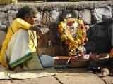 Devadasi with matted hair with a brass bust of goddess Yellamma, Yellamma temple, Saundatti, Karnataka, India