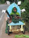 Wooden sculpture of goddess Yellamma with lots of green bangles and green saree at a roadside in Karnataka