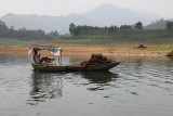 Femme pêchant sur le lac Thac Ba