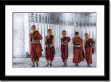 Five young monks in long temple corridor