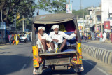 Two mustachioed men in turbans in the back of a three-wheeler, Telangana