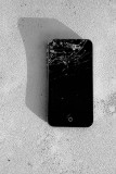 Dead iPhone atop a telephone utility box by the sidewalk