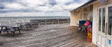Two ladies sit on Cromer Pier on an English summer's day