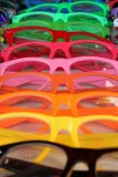 Neon-colored unglasses for sale at a sidewalk display.