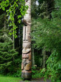 A totem peaks out of the forest in Sitka, AK