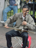David is playing the Erhu Chinese Fiddle.  I only know this because I bought his CD. (grin)  If you are in my 7th grade class, you will learn to love it or else...