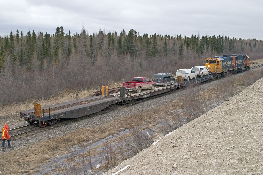 Flatcars from vehicle loading ramp head out before being backed into yard