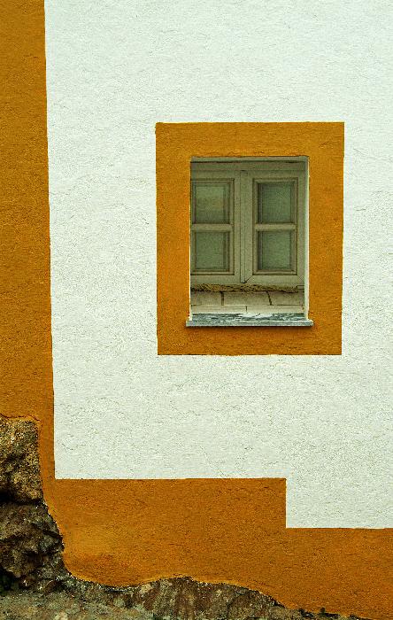 Yellow window, white wall, steep street