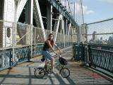 TU member Judy, astride her Brompton, smiles for the camera at the Manhattan tower of the Manhattan Bridge