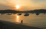 Silhouette of boy running at Pittwater sunset