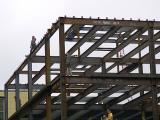 Workers walking on girders during construction of an addition to Kent Hall - Kent State University 6-03