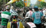 Trudy Hutter (in yellow), Steve Klein (in green & white wool jersey) and Hannah Borgeson (in blue) look on as one of the tour characters, dressed as a policeman (complete with badge and nightstick) inspects bicycles and keeps the crowd in line.
