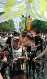 Alex Escalera (in saffron shirt) and Nadette Stasa (red pinwheels in her helmet) get a few minutes respite from the bright sun as the crowd advances down the boulevard to the start line chutes.
