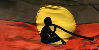 Aboriginal flag with didgeridoo busker in silhouette
