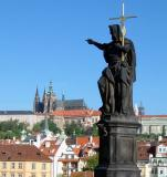 A Charles Bridge Statue points the way to Prague Castle