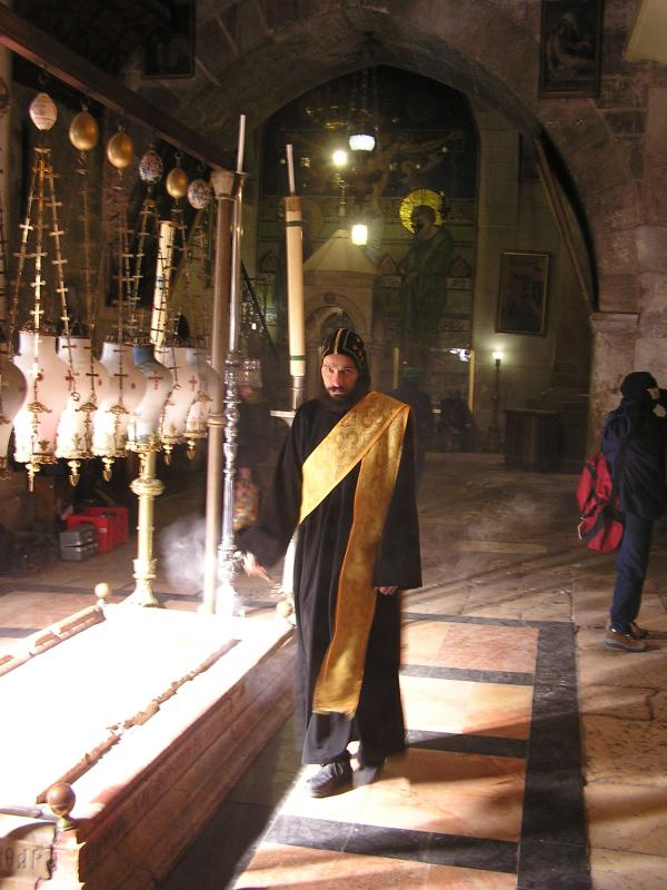 Holy Person marching around church with incense past the Stone of the Unction
