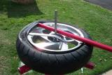 Use the flat end of the tool to remove the old tire from the rim.  Go clockwise.  Notice upper arm of stand has been removed