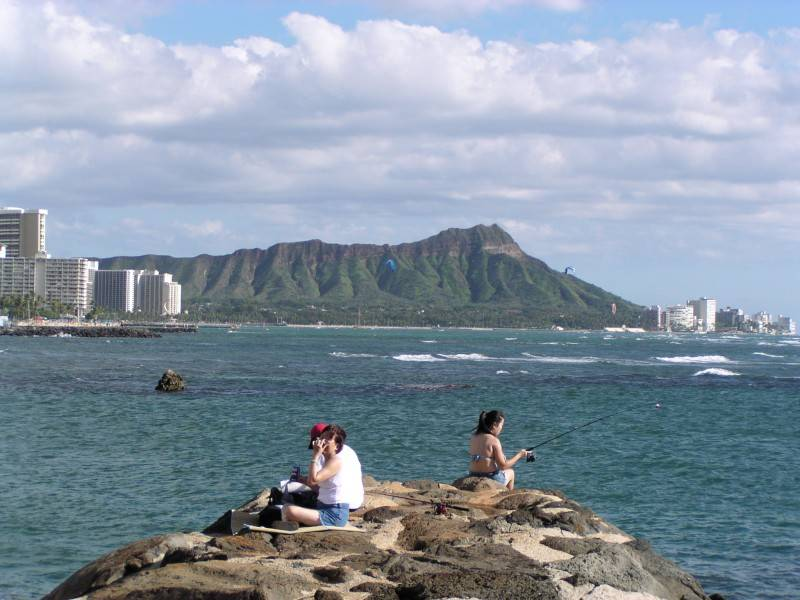 View of Diamond Head as a backdrop for anglers at Ala Moana Beach Park Harbor side.