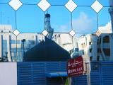 Sign outside of hotel and reflection of the mosque
