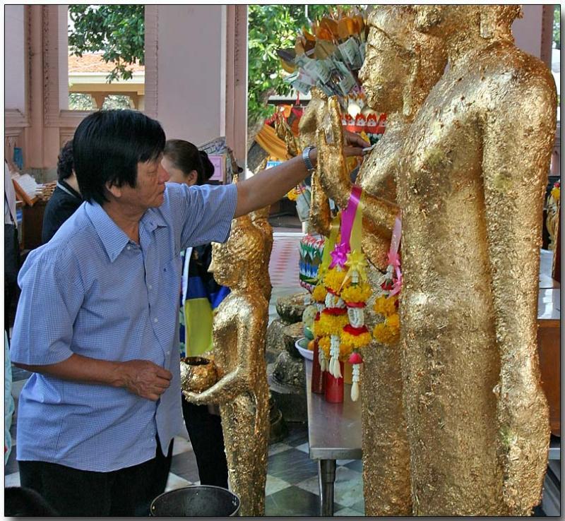 Applying gold leaf to an idol - Prapatom Chedi
