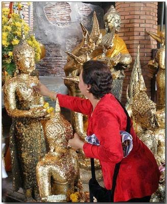 Applying gold leaf to an idol - Wat Chaimongkhon