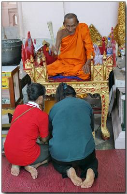 Temple monk at the Prapatom Chedi blessing the faithful