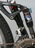 Close up of the rear suspension on a Trek Fuel 100, a dual suspension mountain bicycle.  The frame is aluminum and carbon fiber.
