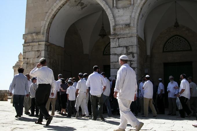 Jewish visitors walk past the Al Aqsa mosque.