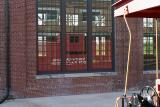 A caboose reflected in one of the Back Shop's windows. The caboose is open so that visitor can walk through it.