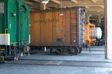 Rail cars in maintenance bays in the roundhouse. Some have been restored, some are waiting to be restored.