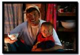 A bowl of tea in one hand and his son in the other, Bayan-Olgii Aimag