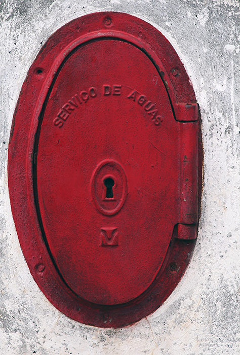 Red water service in gray wall