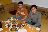 Masa and me eating some dog meat!  The plate in front of me with green veggies and meat is it!  Mmm, Lassie tastes good...
