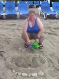 Julia making a sand castle on a rainy day
