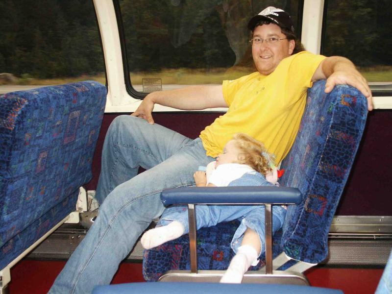 Lilli asleep on the train with daddy.jpg