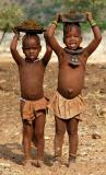 Himba children collecting manure